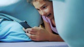 Portret śliczna dziewczyna pod koc z smartphone mała dziewczynka bawić się grę online pod styl życia ogólnospołeczni środki zdjęcie wideo