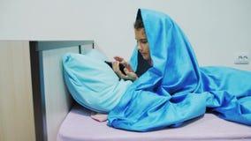 Portret śliczna dziewczyna pod koc z smartphone mała dziewczynka bawić się gry online pod ogólnospołeczną medialną koc zdjęcie wideo