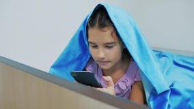 Portret śliczna dziewczyna pod koc z smartphone mała dziewczynka bawić się gry online pod ogólnospołeczną medialną koc dziewczyna zbiory wideo