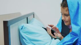 Portret śliczna dziewczyna pod koc z smartphone mała dziewczynka bawić się gry online pod ogólnospołeczną medialną koc zbiory