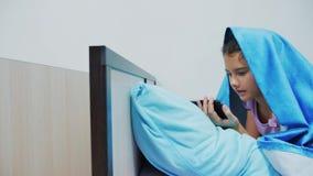 Portret śliczna dziewczyna pod koc z smartphone mała dziewczynka bawić się gry online pod ogólnospołeczną medialną koc dziewczyna zdjęcie wideo