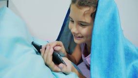 Portret śliczna dziewczyna pod koc z smartphone mała dziewczynka bawić się gry online pod ogólnospołecznym medialnym styl życia zbiory