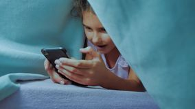 Portret śliczna dziewczyna pod koc z smartphone mała dziewczynka bawić się online styl życia gry pod ogólnospołeczni środki zdjęcie wideo