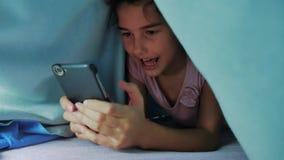 Portret śliczna dziewczyna pod koc z smartphone mała dziewczynka bawić się styl życia gry online pod ogólnospołeczni środki zbiory wideo