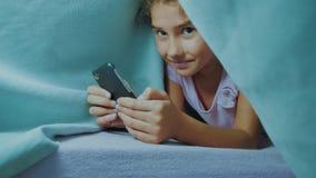 Portret śliczna dziewczyna pod koc z smartphone mała styl życia dziewczyna bawić się gry online pod ogólnospołeczni środki zbiory wideo