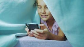 Portret śliczna dziewczyna pod koc z smartphone małej dziewczynki styl życia bawić się gry online pod ogólnospołeczni środki zdjęcie wideo