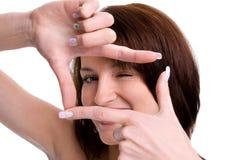 Portret śliczna młoda kobieta tworzy ramę z ona ręki Obrazy Stock