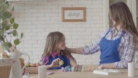 Portret ?liczna ma?a dziewczynka trzyma Easter jajka pozycj? z mam? przy Easter sto?em w kuchni szcz??liwa rodzina zbiory wideo