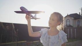 Portret śliczna mała dziewczynka trzyma małego zabawka samolot w górę Dziecko wydaje czas outdoors w podwórko zbiory wideo