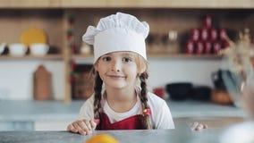 Portret śliczna mała dziewczynka w kuchni ubierającej jako fachowy kucbarski patrzeć i ono uśmiecha się w kamerę zbiory