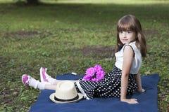 Portret śliczna mała dziewczynka w sukni, siedzi w trawie obrazy stock