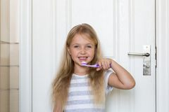 Portret śliczna mała dziewczynka z blondynka włosy który czyści ząb z muśnięciem i pastą do zębów w łazience zdjęcie royalty free