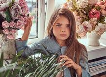 Portret śliczna mała dziewczynka z długim brown włosy i przebijanie spoglądamy będący ubranym elegancką suknię, pozuje z kwiatami Zdjęcia Stock