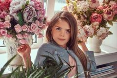 Portret śliczna mała dziewczynka z długim brown włosy i przebijanie spoglądamy będący ubranym elegancką suknię, pozuje z kwiatami Obraz Royalty Free