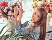 Portret śliczna mała dziewczynka z długim brown włosy i przebijanie spoglądamy będący ubranym elegancką suknię, pozuje z kwiatami Zdjęcie Royalty Free