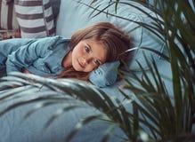 Portret śliczna mała dziewczynka z długim brown włosy i przebijanie spoglądamy, kłamający na kanapie w domu samotnie Obrazy Stock