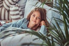 Portret śliczna mała dziewczynka z długim brown włosy i przebijanie spoglądamy, patrzejący kamerę, kłama na kanapie w domu Obraz Royalty Free