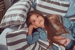 Portret śliczna mała dziewczynka z długim brown włosy i przebijanie spoglądamy, patrzejący kamerę, kłama na kanapie w domu Zdjęcie Stock