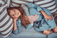 Portret śliczna mała dziewczynka z długim brown włosy i przebijanie spoglądamy, patrzejący kamerę, kłama na kanapie w domu Obraz Stock