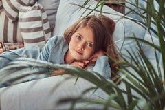 Portret śliczna mała dziewczynka z długim brown włosy i przebijanie spoglądamy, patrzejący kamerę, kłama na kanapie w domu Zdjęcia Stock