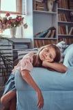 Portret śliczna mała dziewczynka z długim brown włosy i przebijanie spoglądamy, patrzejący kamerę, kłama na kanapie w domu Fotografia Stock