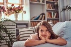 Portret śliczna mała dziewczynka z długim brown włosy i przebijanie spoglądamy, patrzejący kamerę, kłama na kanapie w domu Obrazy Royalty Free