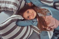 Portret śliczna mała dziewczynka z długim brown włosy, przebijający spojrzenie i powabnego uśmiech, patrzejący kamerę, kłama na a Obraz Royalty Free