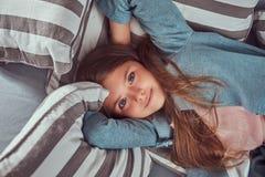 Portret śliczna mała dziewczynka z długim brown włosy, przebijający spojrzenie i powabnego uśmiech, patrzejący kamerę, kłama na a Obraz Stock