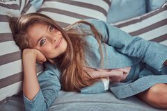 Portret śliczna mała dziewczynka z długim brown włosy, przebijający spojrzenie i powabnego uśmiech, patrzejący kamerę, kłama na a Fotografia Royalty Free