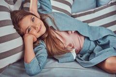 Portret śliczna mała dziewczynka z długim brown włosy, przebijający spojrzenie i powabnego uśmiech, patrzejący kamerę, kłama na a Fotografia Stock