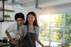 Portret śliczna szczęśliwa para w fartuch akcji szczęśliwego przeniesienia kulinarnym śniadaniu w nowożytnym kitche obraz stock