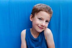 Portret śliczna uśmiechnięta młoda chłopiec z niebieskimi oczami i być ubranym błękitnego wierzchołek na błękitnym tle zdjęcie royalty free