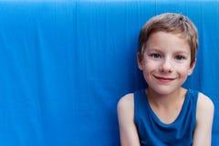 Portret śliczna uśmiechnięta młoda chłopiec z niebieskimi oczami i być ubranym błękitnego wierzchołek na błękitnym tle fotografia stock