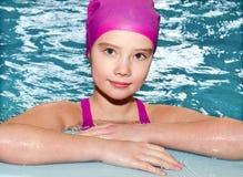 Portret śliczna uśmiechnięta małej dziewczynki dziecka pływaczka w różowym pływackim kostiumu i nakrętce w basenie zdjęcia royalty free