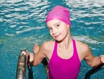 Portret śliczna uśmiechnięta małej dziewczynki dziecka pływaczka w różowym pływackim kostiumu i nakrętce w basenie zdjęcie royalty free