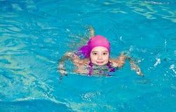 Portret śliczna uśmiechnięta małej dziewczynki dziecka pływaczka w różowym pływackim kostiumu i nakrętce w pływackim poo zdjęcia stock