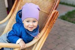 Portret śliczna urocza caucasian chłopiec ma zabawy obsiadanie w drewnianym rattan kołysa krzesła na domu tarasu podwórko outdoor zdjęcia stock