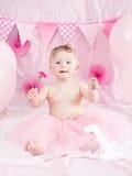 Portret śliczna urocza Kaukaska dziewczynka świętuje jej pierwszy urodziny z smakosza tortem z niebieskimi oczami w różowej spódn Fotografia Stock