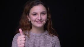 Portret ślicznej młodej brunetki z włosami uczeń robi w górę znaka pokazywać jak i szacuneku na czarnym tle zbiory