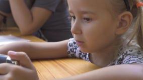 Portret ślicznej małej dziewczynki telefonu komórkowego przyglądający obsiadanie przy stołem Zamyka w górę twarzy śmiesznej dziew zbiory wideo