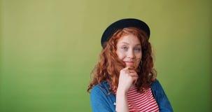 Portret ślicznej nastoletniej dziewczyny wijący włosy wokoło palcowy uśmiecha się flirtować zbiory
