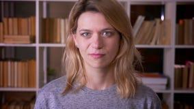 Portret śliczni w średnim wieku blondynka nauczyciela zwroty przewodzi negatywnie w kamerę nie zgadzać się przy biblioteką zdjęcie wideo