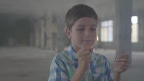 Portret śliczny chłopiec położenia ogień dopasowanie podczas gdy stojący w dymiącym pokoju zdjęcie wideo