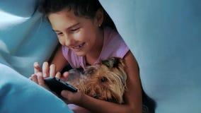Portret śliczny dziewczyny i psa zwierzę domowe pod koc z smartphone mała dziewczynka i pies migdalimy bawić się gry online pod a zbiory