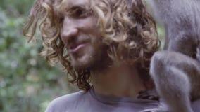 Portret śliczny młody człowiek z długim kędzierzawym włosy i małpa na jego brać na swoje barki zbiory wideo