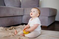 Portret śliczny małe dziecko z jeden żółtym jabłkiem, siedzi na podłodze Dziewczynka 9 miesięcy stary mienie owoc fotografia royalty free