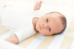 Portret śliczny nowonarodzony dziecka lying on the beach w łóżkowej i patrzeje kamerze Obraz Stock