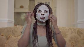 Portret śliczny piękny amerykanin afrykańskiego pochodzenia kobiety kładzenie nawilża twarzową maskę na jej twarzy na trenerze w  zbiory wideo