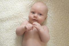 Portret śliczny uśmiechnięty nowonarodzony dziecko przeciw białej baranicie obraz royalty free