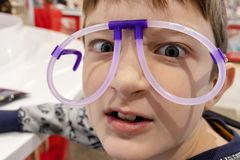 Portret śmieszna śliczna chłopiec jest ubranym dziwacznych szkła robić fluorescencyjne neonowe tubki, centrum handlowe zdjęcia royalty free